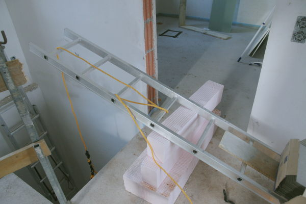 A makeshift crane with a ladder and some tiles as counterweight