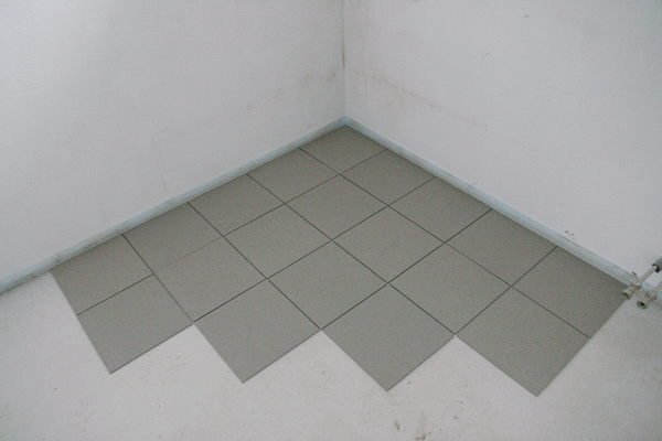 Some tiles placed in the corner of a room.