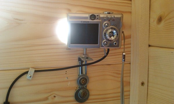 Camera bolted on a metal platform at the wall