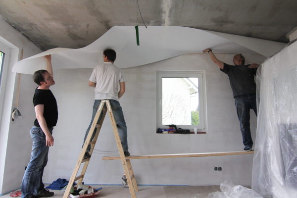 Three people putting wallpaper on