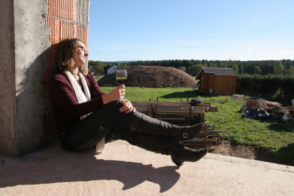 Manu sitting at the bare brickwork the with a glas of wine in the bright shining sun.